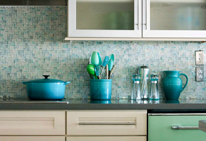 turquoise and pale blue, glass mosaic tile backsplash, in a kitchen with cream, and pale green cabinets, and a dark grey counter top