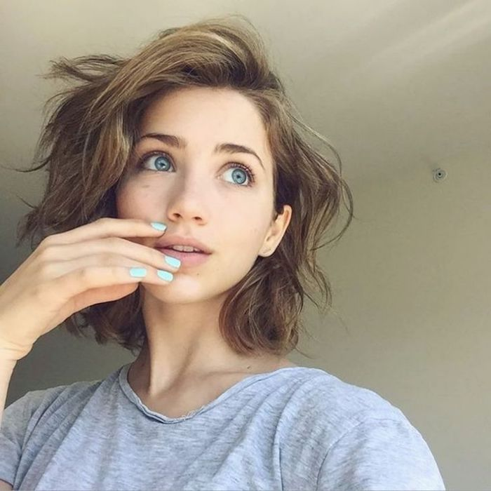 feathery and wavy, chestnut brown hair, with highlights and bangs swept to one side, on young girl with blue eyes, wearing a light grey t-shirt, short sassy haircuts