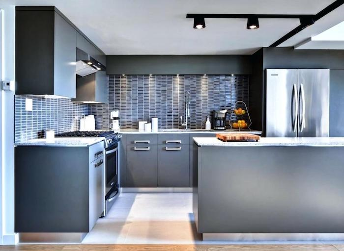 modern kitchen with grey cabinets, metal fridge and a light floor, walls covered with a bluish-grey subway tile pattern