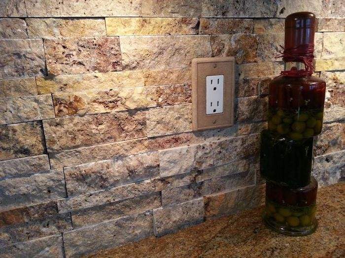 olives marinated in a bottle, on a beige spotted, stone-like counter top, near a stacked stone backsplash, in orange and beige, with a power outlet