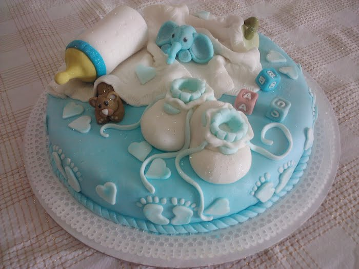 socks for a baby and a white blanket, baby bottle and toys, made from fondant, and topping a round, pale blue cake