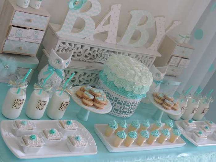 pastries and biscuits, decorated with pale turquoise, and white frosting, bottles with milk and turquoise straws, and a cake in the same colors, on a decorated table, with the word baby in large letters