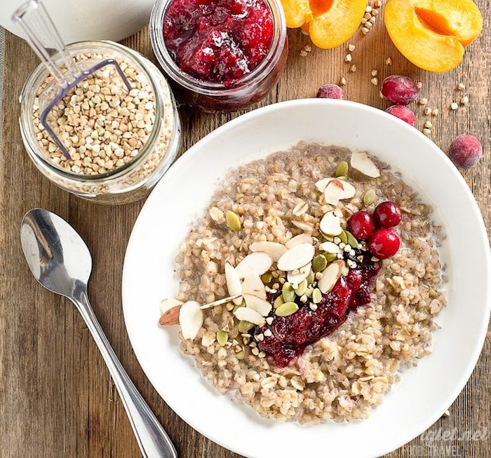 halved apricots and fresh cranberries, near a jar of cranberry sauce, and a jar with buckwheat, low calorie breakfast, bowl with porridge, topped with nuts and cranberries