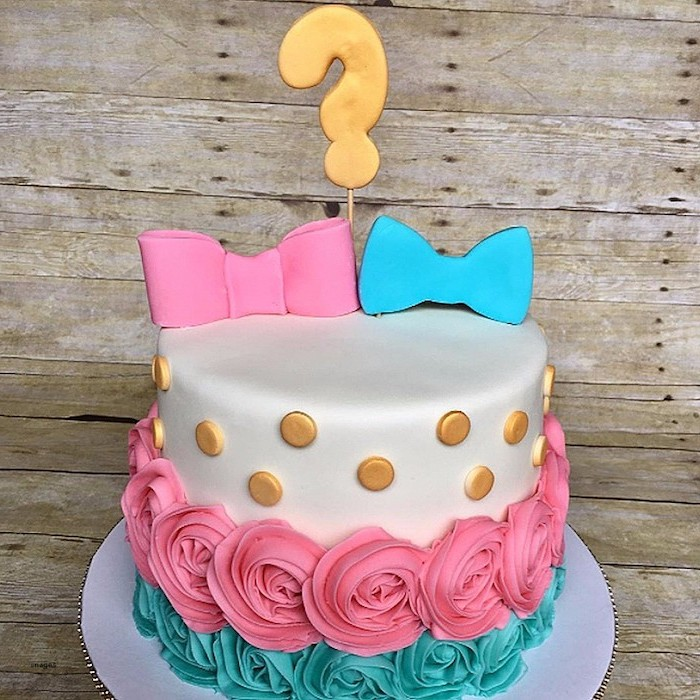 question mark cake topper in gold, placed over two fondant bows, one pink and the other blue, on a white cake, with gold buttons, and pink and teal roses, made from frosting