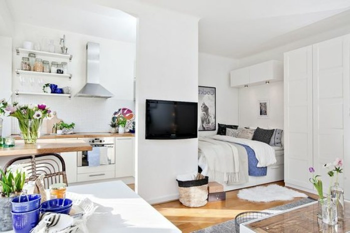 studio flat in white, with a beige laminate floor, room design, containing a sleeping area with bed, a kitchenette, a dining area and a TV