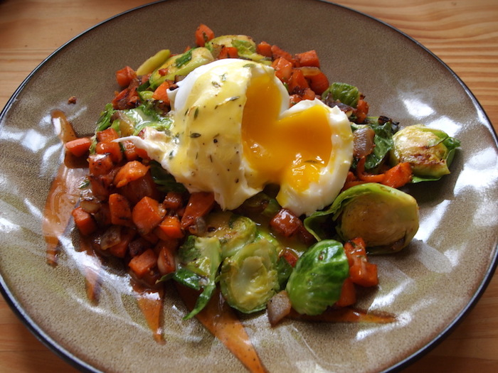 boiled egg cut open and runny, on a bed of cooked vegetables, breakfast menu ideas, Brussels sprouts and carrots, peppers and others