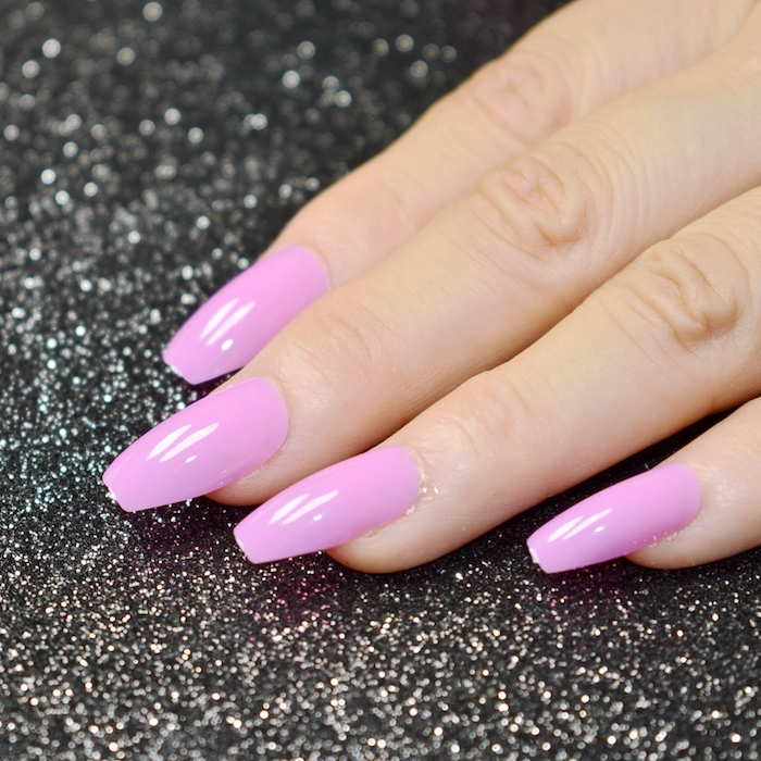 blush pink nail polish, on a hand with four visible coffin shaped nails, resting on a black surface, with silver glitter