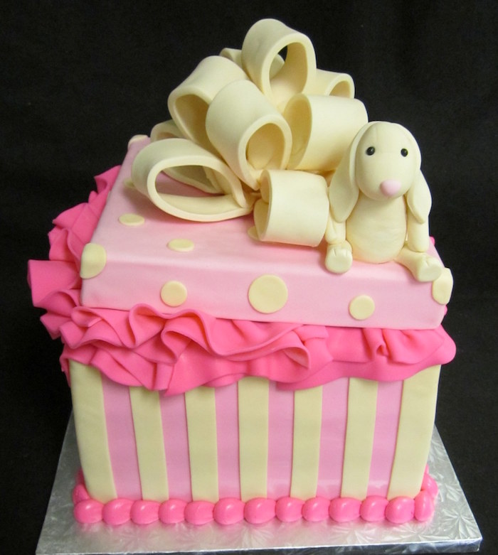 gift-shaped cake in pink, decorated with pale yellow fondant stripes, and polka dots, baby shower cakes for girls, with a large pale yellow bow, and a bunny toy fondant figurine