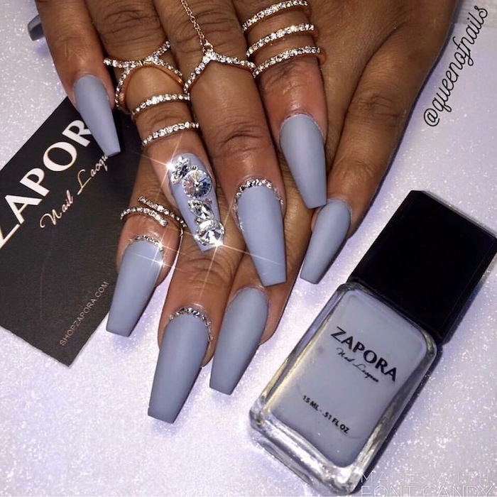 lots of encrusted silver rings, on two brown hands, with long nails, painted in a matte, milky grey nail polish, bottle of the same nail polish nearby