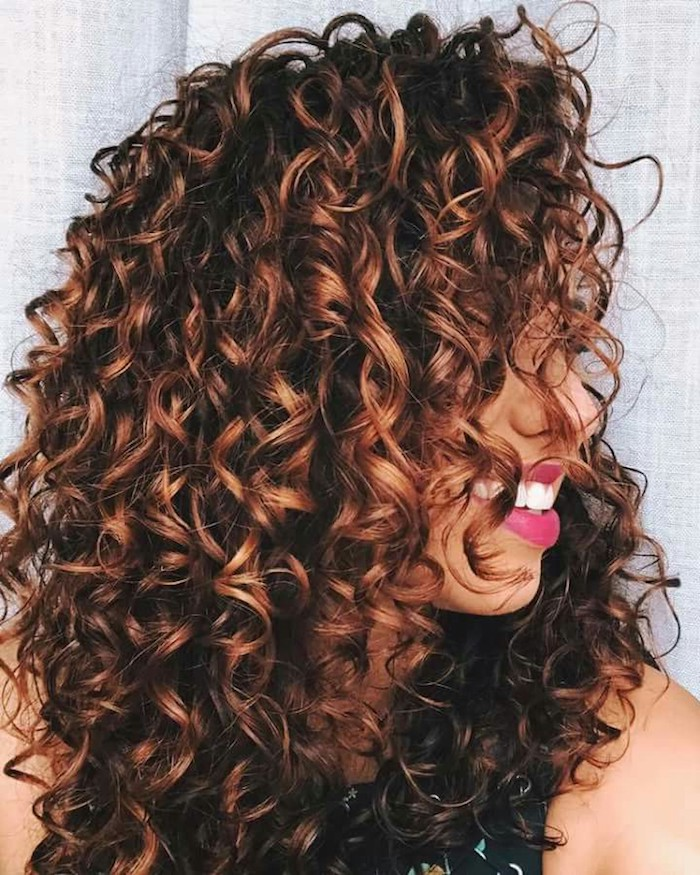 hot pink lipstick, and white teeth, worn by young woman, with dark brunette curly hair, long curly hairstyles, with caramel highlights