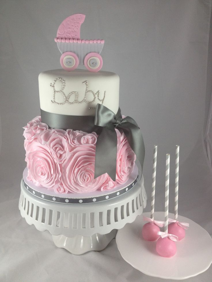 pram figurine in pale grey and pink, on top of a two-layered cake, bottom layer decorated with pink frosted roses, upper layer with the words baby written in silver, baby shower cakes for girls, shiny grey bow, and three cake pops