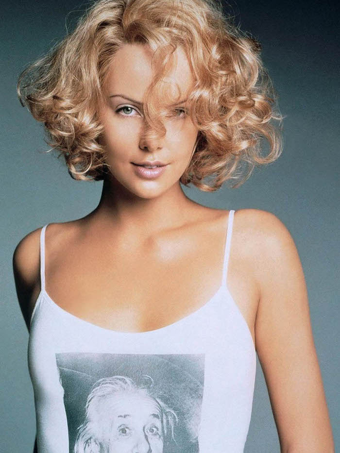strappy white top, with greyscale print of albert einstein, worn by charlize theron, with messy blonde bob, short haircuts for curly hair, a strand falling on her forehead