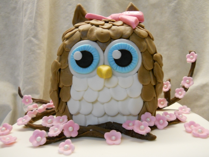 beige and white owl, with large blue eyes, made from fondant, owl baby shower cake, on a few brown fondant branches, decorated with pink cherry blossoms