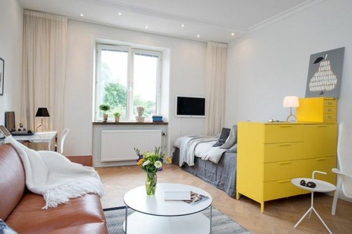 leather sofa in brown, with a white throw, near a round white coffee table, inside a room with a laminate floor, a bed and a yellow chest of drawers