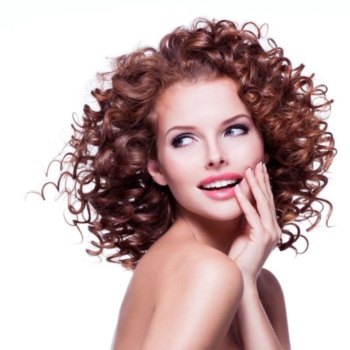 slim young woman, with bare shoulders, wearing glossy pink lipstick, curly shoulder-length hair, brunette and glossy, hairstyles for curly hair, pale eye make up