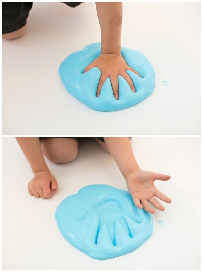 small child pressing his or ehr hand, into a large pile of blue, fluffy slime, placed on a smooth, white surface or floor