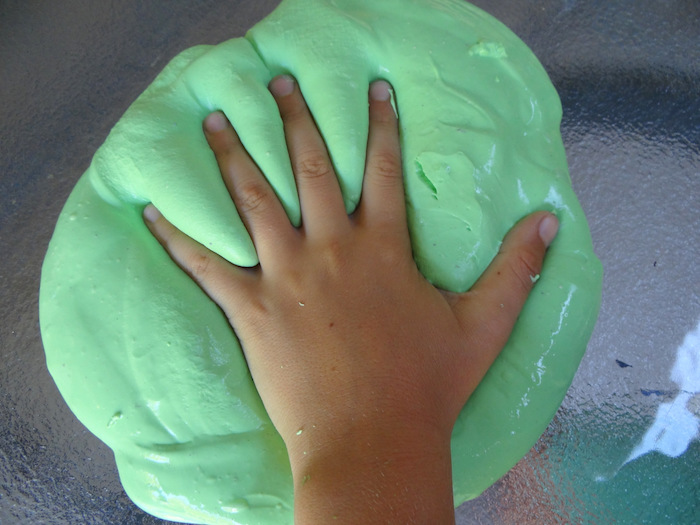 kid pressing his or her hand, on a pile of soft, foamy and gooey substance, how to make slime without borax, placed on a glass surface