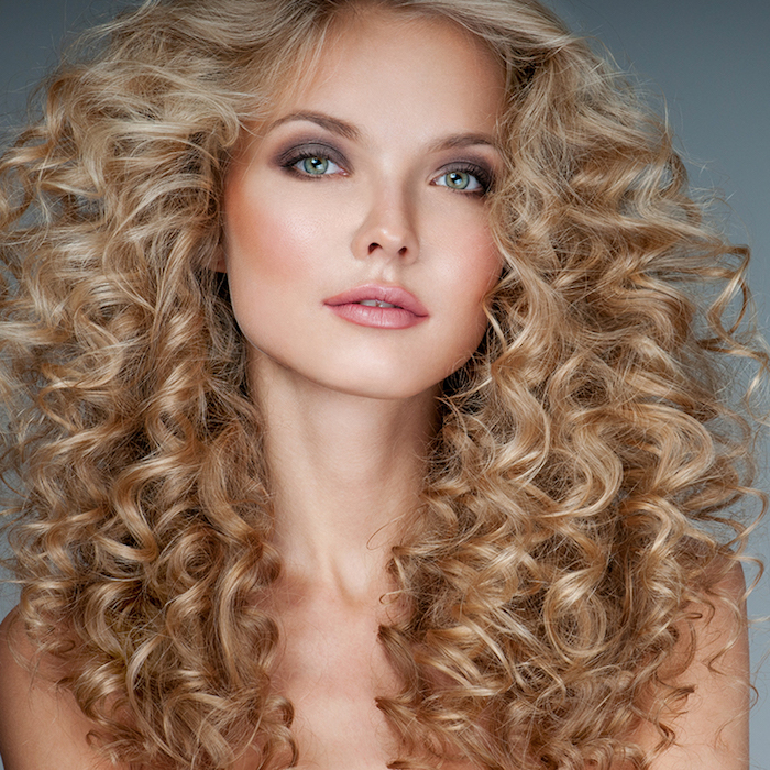 straw blonde voluminous and curly hair, with slightly darker tips, hairstyles for curly hair, worn by young woman, with glossy pink lipstick, and purple eye shadow