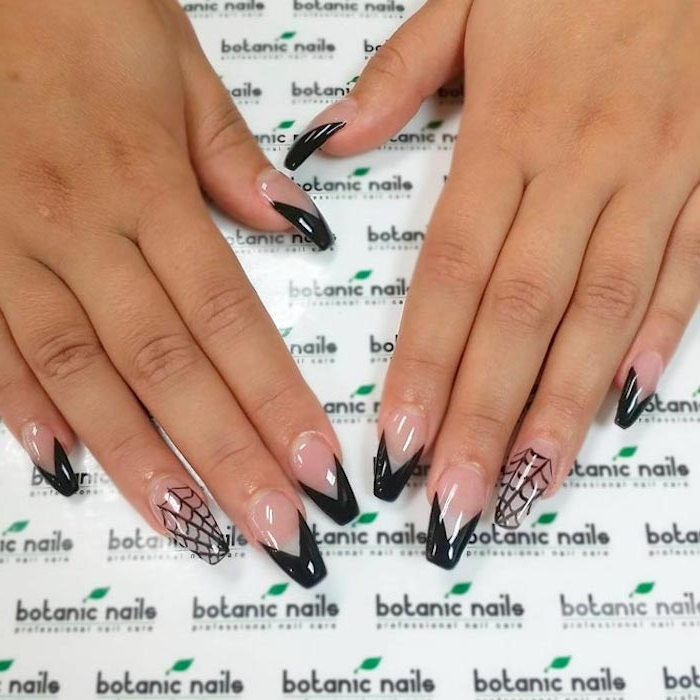 spider webs and geometric shapes in black, on two hands, with clear ballerina nail shape, resting on a white patterned surface