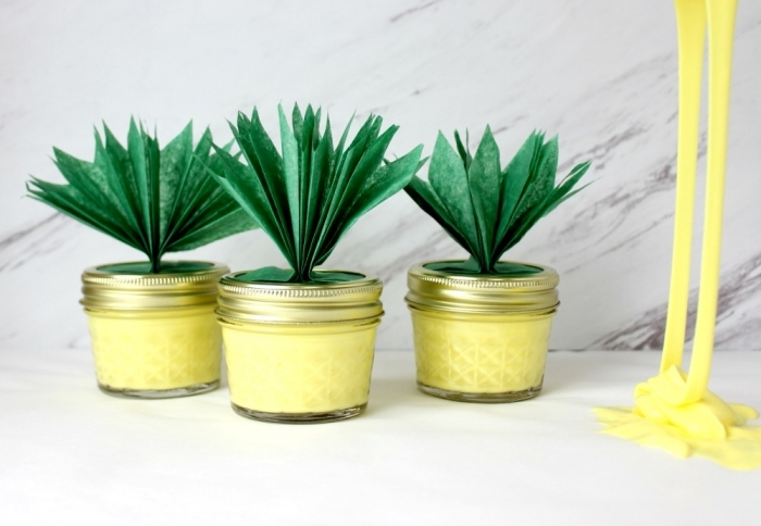 pineapples made from small jars, with green paper leaves, stuck to their lids, all jars are filled with yellow goo, how to make slime with glue, more yellow goo nearby