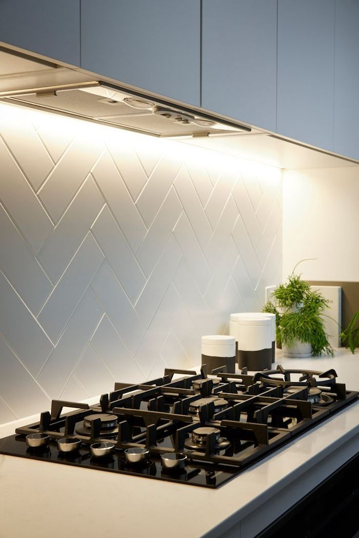 hob with a black surface, inbuilt in a white counter top, with a white herringbone backsplash, pale grey kitchen cabinets