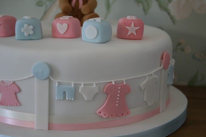 smooth white frosting, on a cake seen in close up, decorated with building blocks, in pastel pink and pale blue, with little clothes line, featuring small white blue and pink clothes, made from fondant