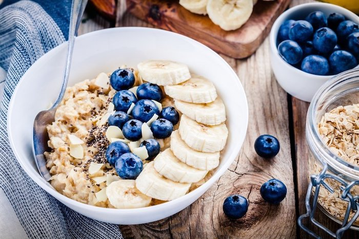 flakes of almond and coconut, on top of a creamy porridge, with sliced banana, and whole blueberries, simple breakfast ideas, ingredients in different containers nearby