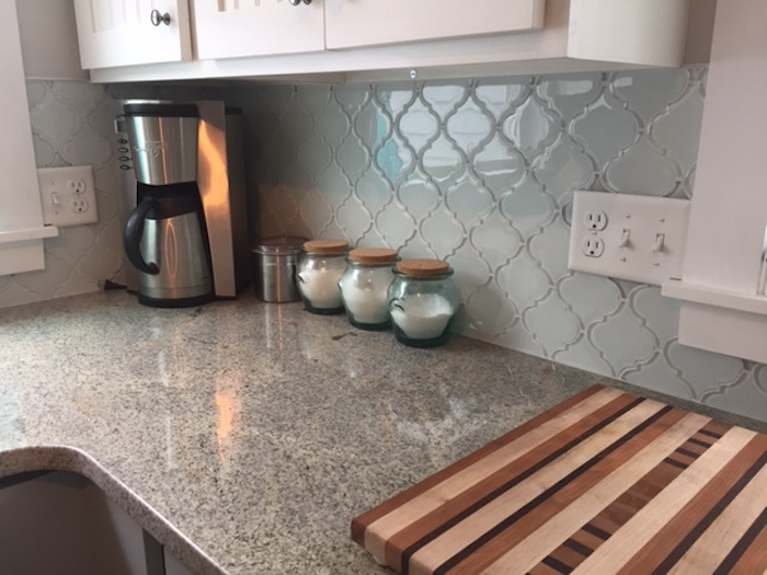chopping board and three small jars, on a spotted beige counter top, near white cabinets, pale blue arabesque backsplash, and a coffee machine