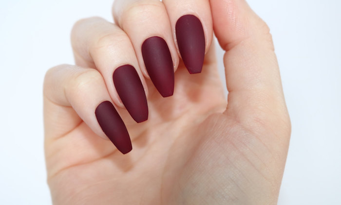 burgundy red matte coffin nails, attached to a pale hand, with folded fingers, seen in close up, on a plain white background