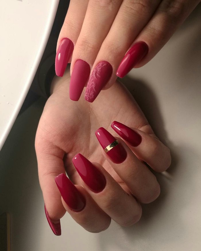 glossy and matte nail polish, in red hues, on two hands with acrylic nail shapes, one nail is decorated with a gold metallic stripe, wile another has a floral acrylic motif