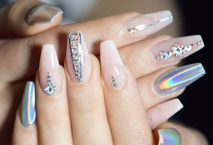 hologram-effect nail polish, on four fingers, the other six are painted in a very pale, baby pink color, and decorated with rhinestones, coffin nail designs