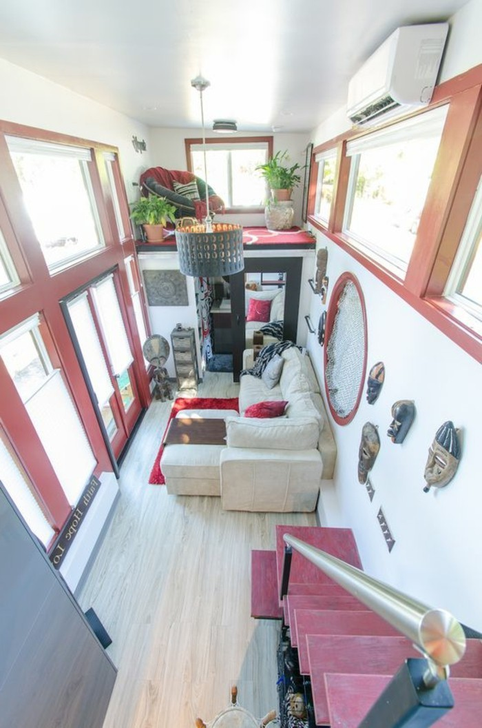 red accents inside a two story home, with a small beige corner sofa, living room furniture for small spaces, various decorations and potted plants, red armchair and several windows