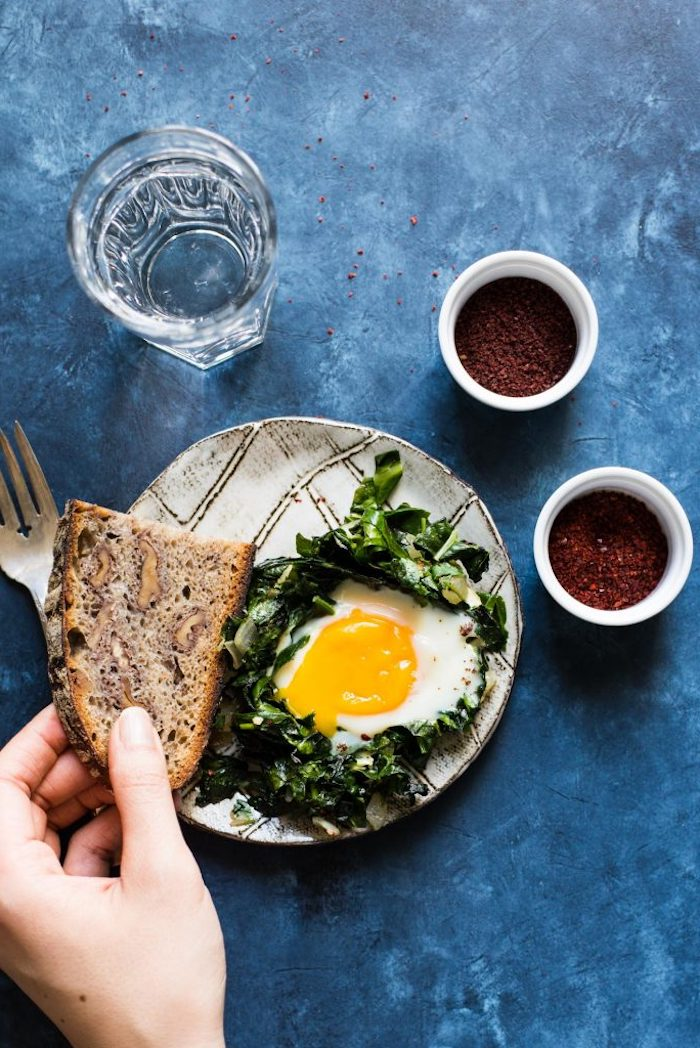 hand holding a piece of full grain bread, near a plate containing spinach, and a sunny side up egg, breakfast menu ideas, glass of water and condiments