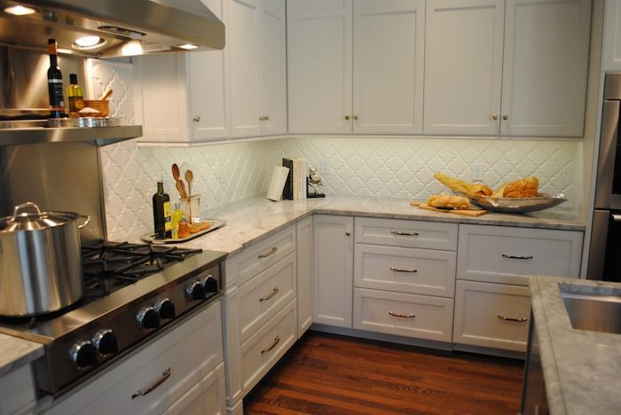 extractor hood and stove, with a large metal cooking pot, inside a kitchen, with a light blue, arabesque tile backsplash, white cabinets and a brown laminate floor