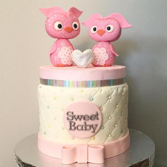 pair of pink owl figurines, placed near a small, white and silver heart, baby shower cake toppers girl, on top of a cream and pink cake, decorated with multicolored pearls, and the words sweet baby