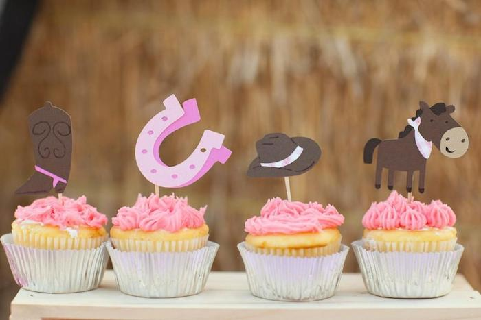 horse in brown, with pink bandana, brown cowboy hat, with pink ribbon, two pink horseshoes, and a brown cowboy boot, with pink spurs, baby shower cake toppers girl, on four pink cupcakes