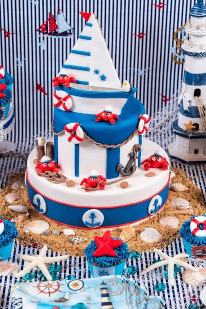 starfish and seashells, strewn around a white and blue cake, decorated with little red sailor crabs, and a small sailing boat, nautical baby shower cakes, various sea-related items