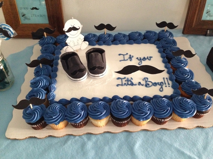 mustache toppers in black, decorating a large white cake, with small dark grey baby shoes, and a smiling baby drawing, baby shower sheet cakes, surrounded by dozens of dark blue cupcakes