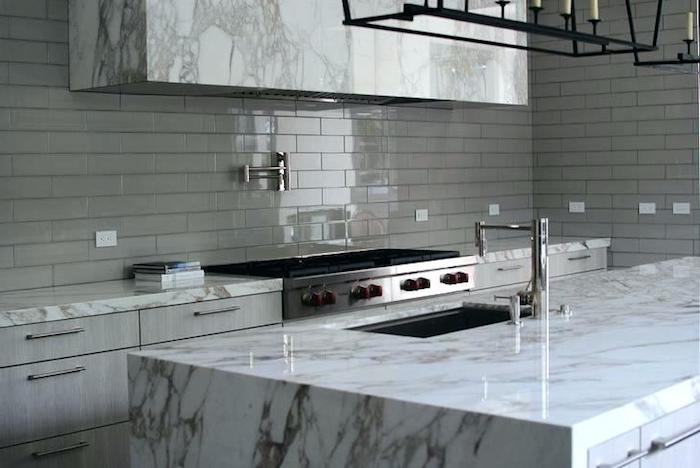 glossy grey subway tile kitchen backsplash, inside a room with marble counter tops, two metal stoves, and pale grey cabinets