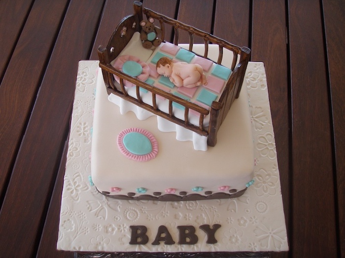 cradle made from brown fondant, containing a checkered blue and pink blanket, pillows and a sleeping baby figurine, on top of a square white cake