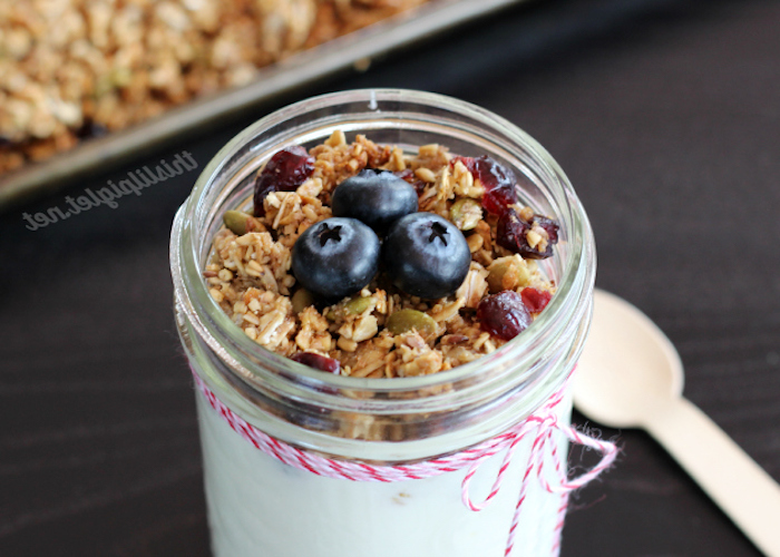 red and white thread, tied around a small jar, containing muesli topped with pumpkin seeds, dried cranberries and fresh blueberries