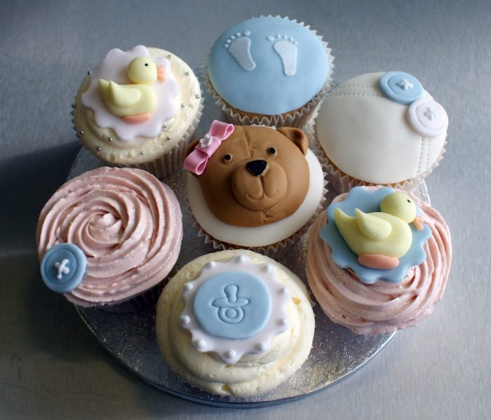seven cupcakes with pale pink, and light yellow frosting, decorated with little fondant shapes, duckling and a teddybear, little footprints and blue and white buttons