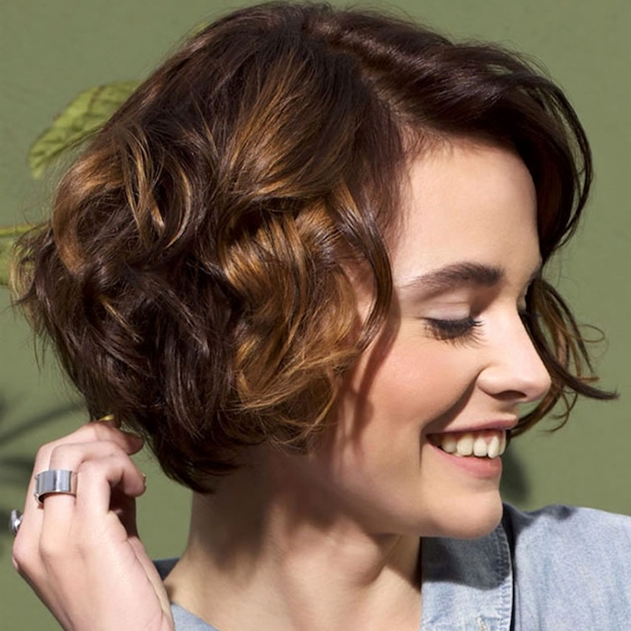 smiling young woman, head turned to one side, wearing a curled bob, with deep side part, short hairstyles for fine hair, in brunette and dark blonde tones