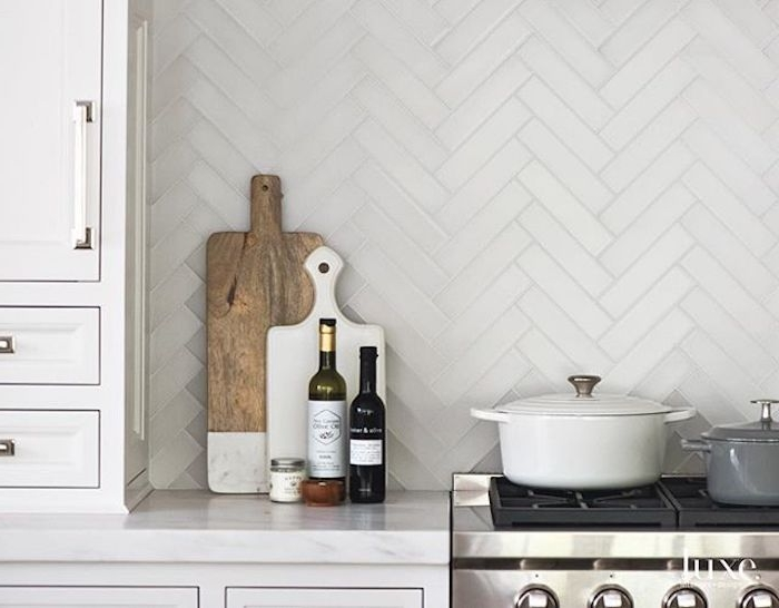 two cooking pots, on the black hob of a stove, near a marble counter top, with two cutting boards, two bottles and a small jar, white kitchen backsplash, with a herringbone pattern