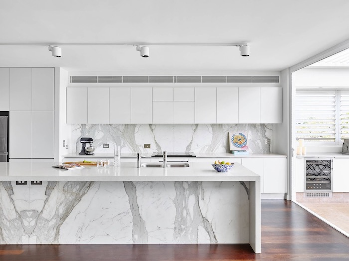 bright spacious kitchen, with smooth white cabinets, dark brown floor, white kitchen island, with a marble-effect, and a matching back splash