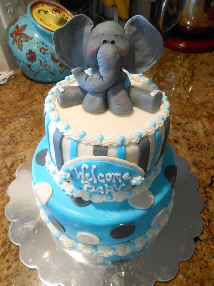 figurine of a baby elephant, made from dark grey fondant, topping a two-layer cake, in pale blue and white, with grey and white polka dots and stripes