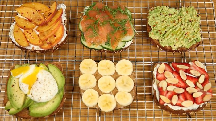 six different kinds of toppings, on pieces of toast, placed on a metal griddle, simple breakfast ideas, peaches and creamed cheese, salmon and cucumber, peanut butter and banana