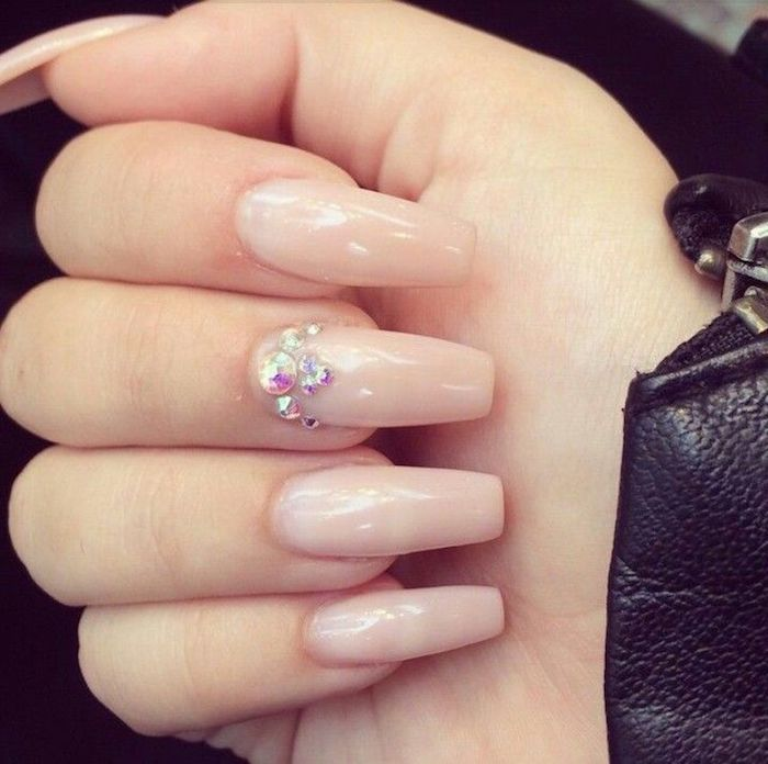 leather sleeve in black, and a pale hand with folded fingers, sporting long coffin-style nails, painted in light, nude pink nail polish, middle finger nail is decorated with rhinestones