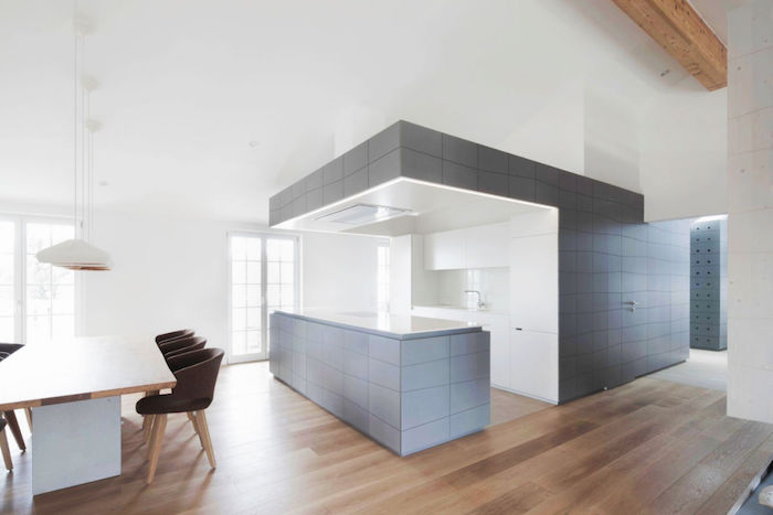 open plan space, in grey and white, with brown laminate floor, and a kitchen area, white kitchen backsplash, large dining table and chairs
