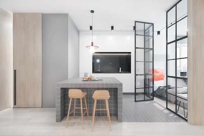 minimalistic kitchen in neutral colors, creamy grey kitchen island, two beige stools, sink with black backsplash, open veranda door
